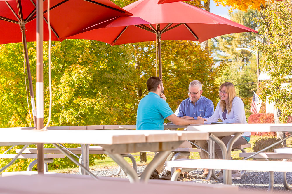3 creare employees sitting at a picnic table with a red umbrella